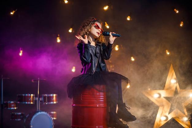 革のジャケットと赤いサングラスを身に着けている巻き毛の美しい少女は、レコーディングスタジオでカラオケのワイヤレスマイクに向かって歌います Premium写真