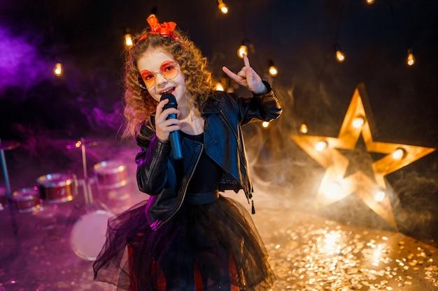 Красивая девушка с вьющимися волосами в кожаной куртке и красных очках поет в беспроводной микрофон для караоке в студии звукозаписи Premium Фотографии