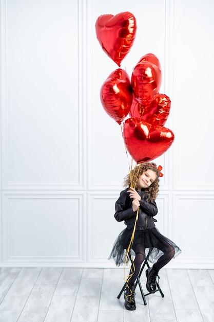 Молодая девушка с красными воздушными шариками Premium Фотографии