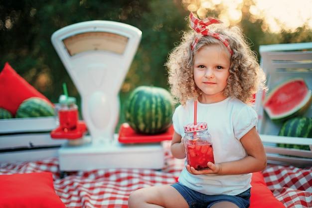夏のさわやかなドリンクとして氷とミントの瓶にスイカレモネードを飲む子供。フルーツ入り冷たいソフトドリンク Premium写真