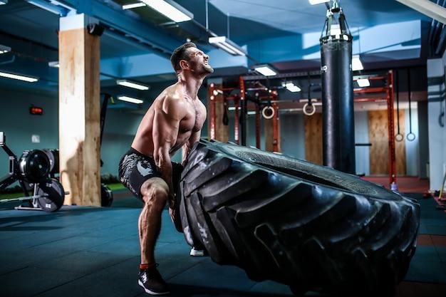 Человек без рубашки переворачивает тяжелую шину Premium Фотографии
