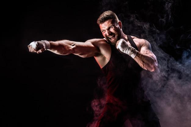 煙と黒い壁で戦うスポーツマンムエタイタイのボクサー。 Premium写真