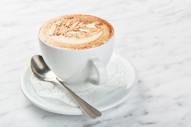 テーブルの上のカプチーノのカップ Premium写真