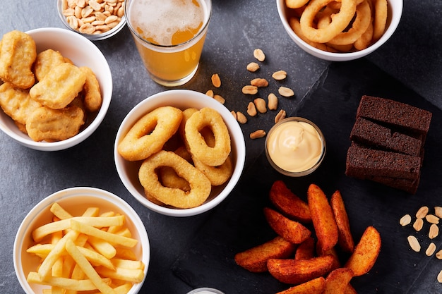 石のテーブルでビールとスナック。ナッツ、チップ。上面図。 Premium写真