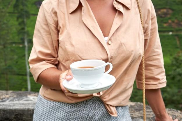 Женщина с чашкой напитка на плантации Premium Фотографии