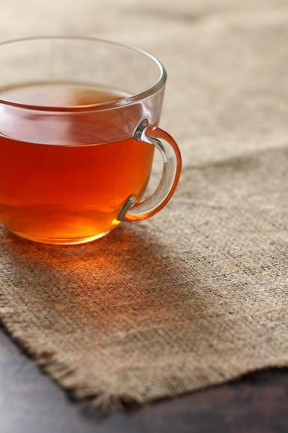 黄麻布のテーブルクロスにガラスの透明なマグカップでお茶。 Premium写真