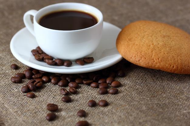 オートミールクッキー、マグカップ、コーヒー、ソーサー、コーヒー豆、黄麻布のテーブルクロスに散在しています。 Premium写真