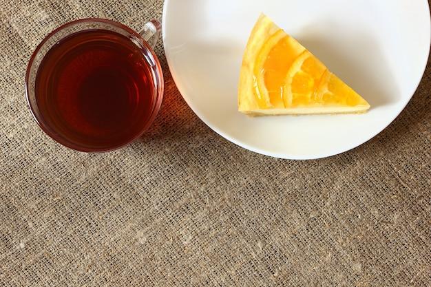 白い皿にオレンジとチーズケーキ、黄麻布のテーブルクロスにお茶とガラスのマグカップ。上面図。 Premium写真