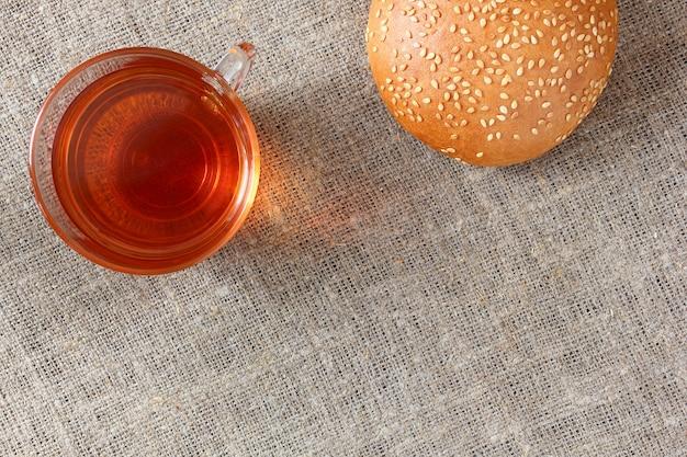 ガラスのマグカップと黄麻布のテーブルクロスにごまパンのお茶。上面図。 Premium写真
