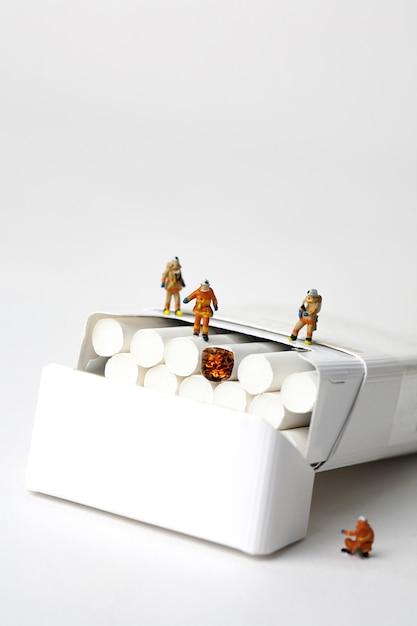 ミニチュア消防士と白い背景の上のタバコ Premium写真