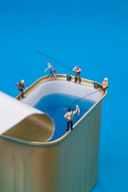 缶で釣りをするミニチュアの人々 Premium写真