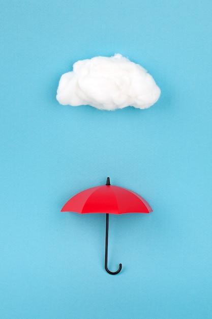 スカイブルーの雲の下で赤い傘 Premium写真