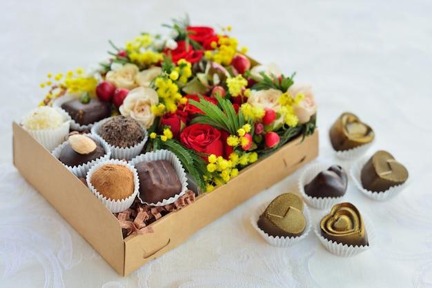 Подарочная коробка с цветами и конфетами из шоколада Premium Фотографии