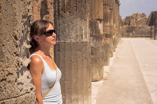 ポンペイ市の遺跡の背後にある若い女性。イタリア Premium写真