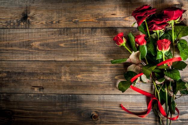休日の背景、バレンタインの日。赤いバラの花束、赤いリボンとネクタイ。木製のテーブルの上 Premium写真