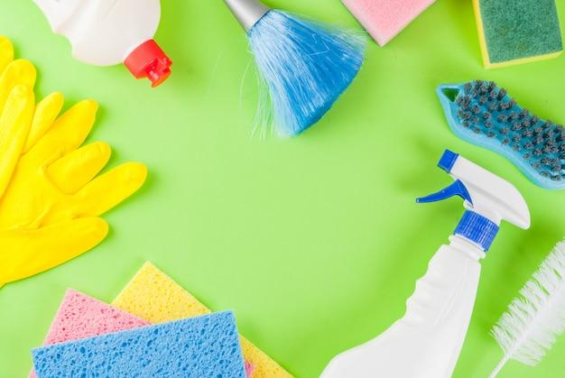 用品、ハウスクリーニング製品の山と春の大掃除のコンセプト。緑の背景トップビューコピースペースフレーム上の家事のコンセプト Premium写真
