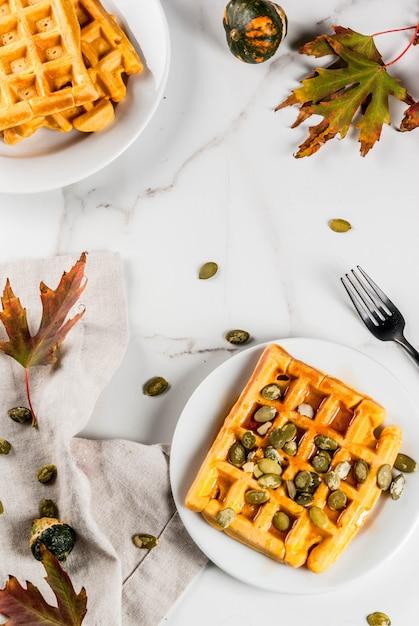 メープルシロップとカボチャの種、白い大理石のテーブルの上に自家製のカボチャワッフル Premium写真