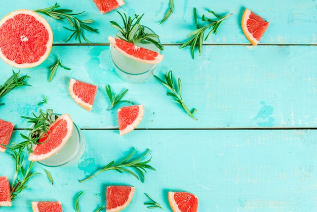 Алкогольный напиток, розмарин, грейпфрут и джин коктейль, на голубом деревянном столе, вид сверху Premium Фотографии