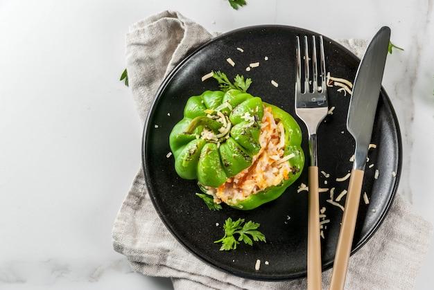 秋のレシピ。ミンチ肉、ニンジン、トマト、ハーブ、チーズを詰めた自家製ピーマン。白い大理石のテーブル、ポーションプレート、ナイフとフォーク、コピースペーストップビュー Premium写真