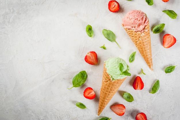 Летние свежие десерты. зеленый базилик и красная клубника мороженое в конусе. на белом каменном столе с листьями базилика и свежей клубникой вокруг. на белом каменном столе. вид сверху копией пространства Premium Фотографии
