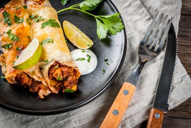 Мексиканская еда. кухня южной америки. традиционное блюдо из острой говяжьей энчиладас с кукурузой, фасолью, помидорами. на противень, на старый деревенский деревянный фон. копировать пространство Premium Фотографии
