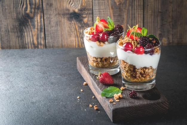 健康的な朝食。夏の果実と果物。グラノーラ、ブラックベリー、イチゴ、チェリー、ミントを使った自家製ギリシャヨーグルト。木製と石の黒いテーブル、メガネ。 Premium写真