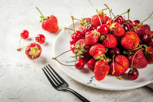 Здоровый завтрак, обед или перекус. летние ягоды и фрукты. органические свежие вишни и клубники вокруг белого мрамора пластины, на белом столе. Premium Фотографии