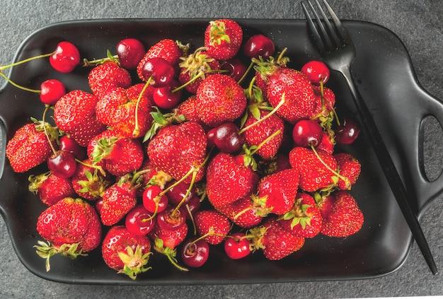Здоровый завтрак, обед или перекус. летние ягоды и фрукты. органическая свежая вишня и клубника на прямоугольном блюде, с вилкой, на черном каменном столе. вид сверху Premium Фотографии