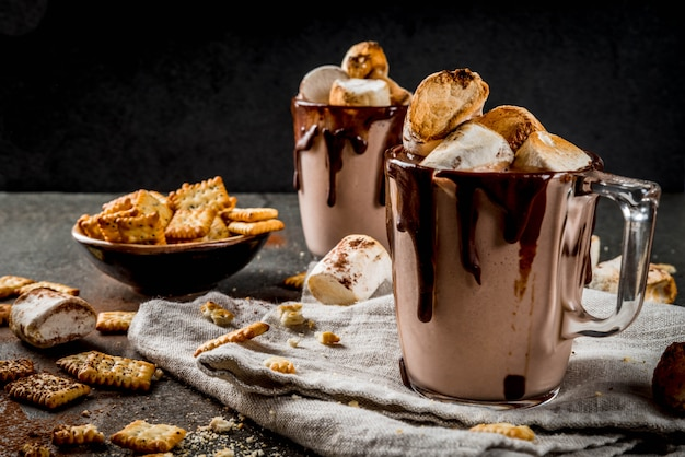 Традиционные осенние и зимние коктейли, алкоголь. коктейль из горячего шоколада «у костра» с солеными крекерами и жареным зефиром, в двух кружках, на черном каменном столе, Premium Фотографии