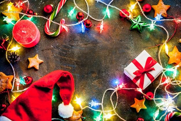 Темный фон рождество с рождественские гирлянды, украшения, пряники звезд, подарочная коробка и шляпу санта и свечи. вид сверху копировать пространство кадра Premium Фотографии