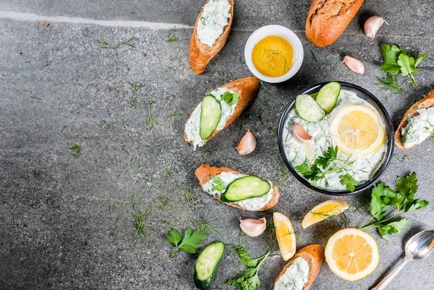 Традиционная кавказская и греческая еда. соус цацики с ингредиентами - огурец, лимон, петрушка, укроп, чеснок. на темном каменном столе. с бутербродами и багетом. вид сверху копией пространства Premium Фотографии