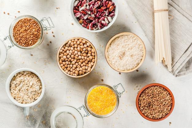 Выбор безглютеновых продуктов, круп: ксантановая камедь. гречка, рис, лапша рисовая, нут, чечевица, кукуруза, фасоль, овсянка. в мисках и банках вид сверху на белом столе сверху копией пространства Premium Фотографии