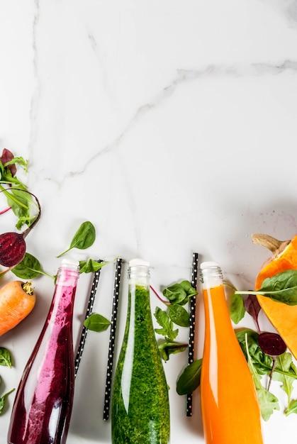 ビーガンダイエット食品。カラフルな新鮮な有機スムージーの選択は、秋野菜と一緒に飲みます:ビートルート、カボチャ、ニンジン、葉物野菜。ボトル、白いテーブル。コピースペースのトップビュー Premium写真