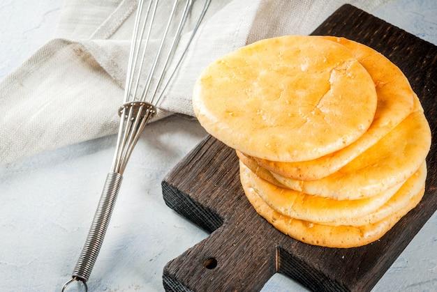 健康的な食事。低グルテングルテンフリーの非アレルギースナックの概念。自家製の焼きたてのトルティーヤは、卵とクリームチーズからパンを曇らせます。明るいコンクリートテーブルコピースペース Premium写真