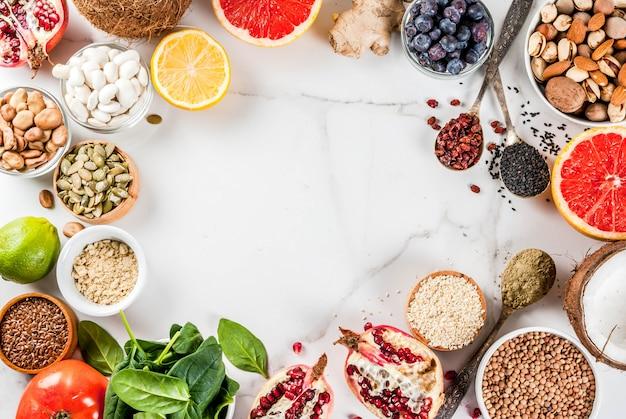有機健康ダイエット食品、スーパーフード-豆、マメ科植物、ナッツ、種子、野菜、果物、野菜のセット。ホワイトバックグラウンドコピースペース。トップビューフレーム Premium写真