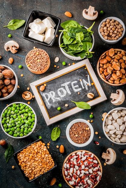 健康的な食事ビーガンフード、野菜たんぱく源:豆腐、ビーガンミルク、豆、レンズ豆、ナッツ、豆乳、ほうれん草、種子。白いテーブルのトップビュー。 Premium写真