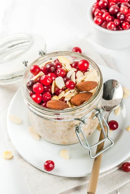 冬の健康的な朝食のレシピ、クリスマスの朝のアイデア。アーモンド、クランベリー、砂糖を一晩オートミール。 。コピースペース Premium写真