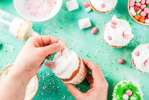 イースターカップケーキを作る、人はバニーの耳とキャンディの卵、フレーム、写真の女の子の手でケーキを飾る Premium写真