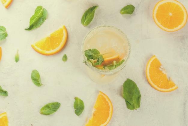 新鮮なオレンジとミントのレモネード、グラスに氷と明るい灰色の石大理石テーブルトップビュー Premium写真