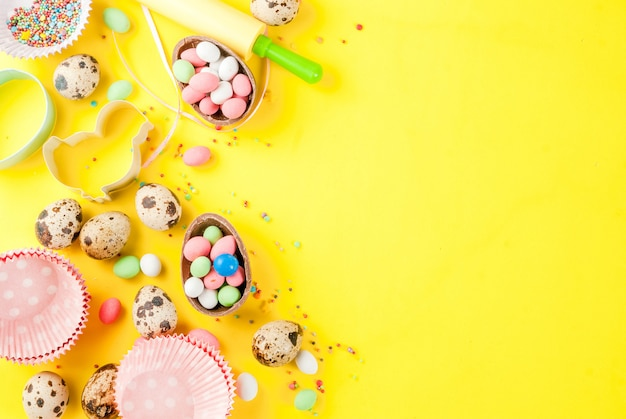 Скалка, венчик для взбивания, формочки для печенья, перепелиные яйца и сахар, посыпанный желтым Premium Фотографии