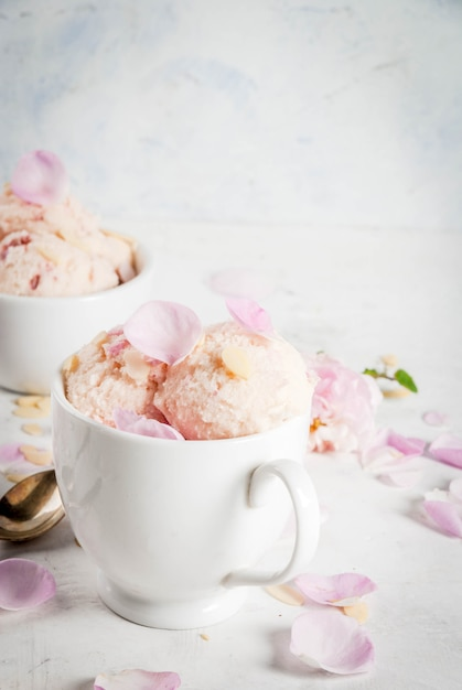Мороженое с лепестками роз и кусочками миндаля в белых сервировочных тарелках Premium Фотографии