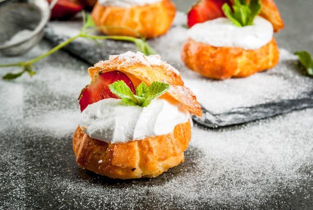 ホイップクリーム、新鮮なイチゴ、ミント、粉砂糖の振りかけでケーキの利益。 Premium写真