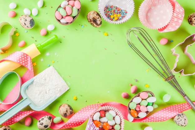 Скалка, венчик для взбивания, печенья, сахарная посыпка и мука на светло-зеленом фоне Premium Фотографии