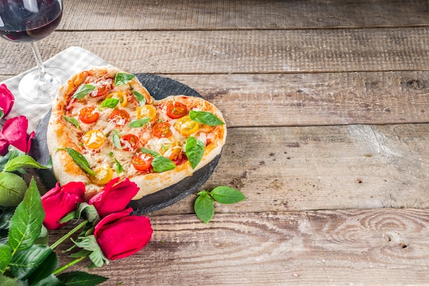 バレンタインデーのためのハート型のピザ Premium写真