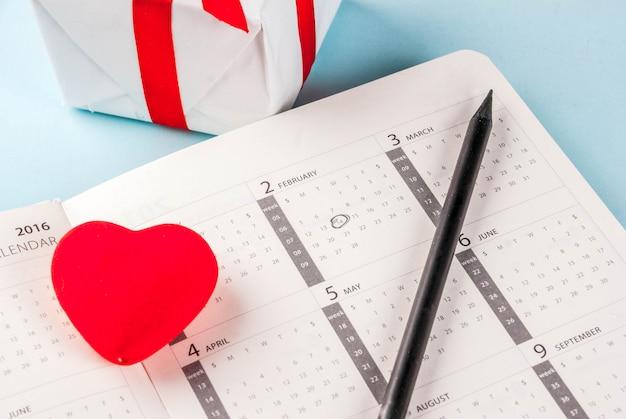 Поздравительная открытка дня святого валентина красное сердце с подарочной коробке за февраль календарь на голубом фоне. скопируйте место для приветствия Premium Фотографии