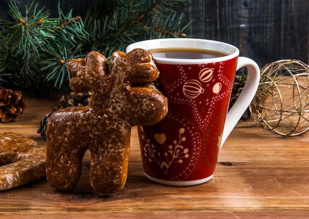 Чашка чая и пряник в виде оленя на деревянном столе. возле елки ветка, шишки и елочные шары. Premium Фотографии