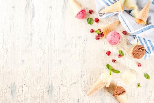 Летние сладкие ягоды и десерты, с разнообразным вкусом мороженого в шишках розового (малинового), ванильного и шоколадного с мятой на светлом бетоне Premium Фотографии