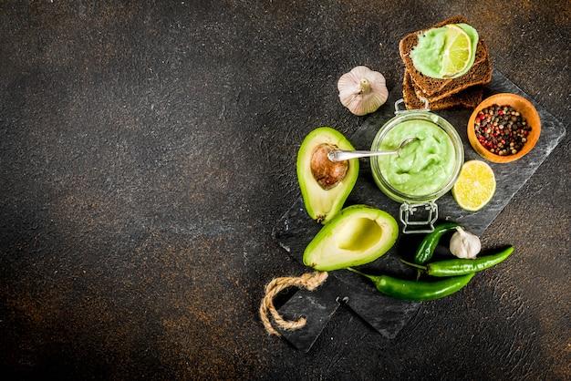 Мексиканская еда, гуакамоле с ржаными тостами бутерброды на темном фоне, копией пространства Premium Фотографии