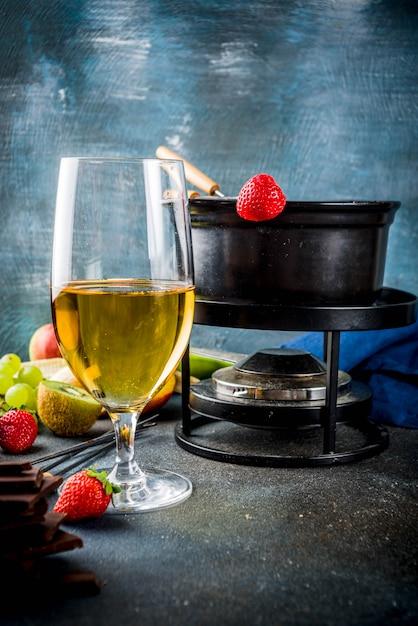 Шоколадное фондю в традиционном горшочке для фондю с вилками, белым вином, различными ягодами и фруктами Premium Фотографии