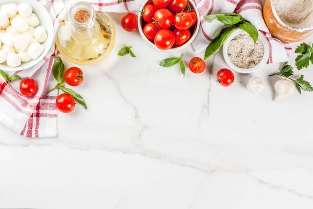 小麦粉、オリーブオイル、バジル、トマト、キッチンアクセサリートップビューで白い大理石のテーブルに自家製パスタピザイタリア料理の食材 Premium写真